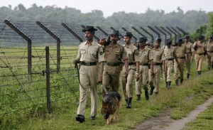 Indian Border Security Force (BSF) personnel patrol with a sniffer dog along a stretch of the India-Bangladesh border ahead of India's Independence Day celebrations in Fulbari village, on the outskirts of the northeastern Indian city of Siliguri, August 12, 2009. Security has been tightened across the nation to ward off any possible militant attacks leading up to India's Independence Day celebrations on August 15. REUTERS/Rupak De Chowdhuri (INDIA MILITARY POLITICS)